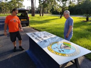 Jeff Strickland and Pat Geer (right) prep the new signs for installation at the Chapel of the High-Speed Pass